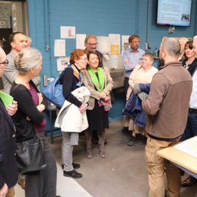 In een van de productiewerkplaatsen krijgen de bezoekende D66'ers uitleg van een van de werkbegeleiders.